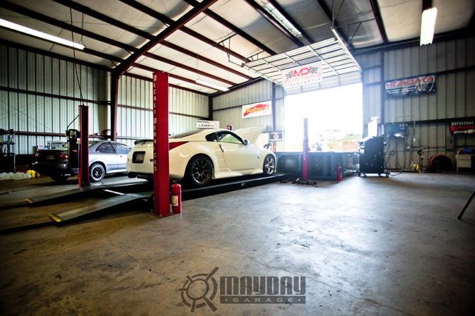 A white Z awaits to be lifted up to the Dyno