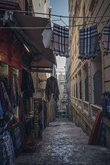 A souvenir shop in an alley (Syahrel Azha Hashim) Tags: valetta street sony 2016 shallow holiday nopeople simple details a7ii clothes hanged ilce7m2 dof building souvenirstore restaurant getaway handheld buildings colorimage vacation prime light naturallight colorful 35mm travel syahrel people architecture malta sonya7 streetphotography outdoor alley detail