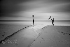 (Claire Hutton) Tags: longexposure sea people blackandwhite bw woman beach water girl clouds umbrella person stream post horizon windy pole groyne ndfilter 10stop nd1000 nd110 bw110