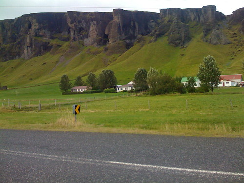 an icelandic farm with icelandic bluffs behind it