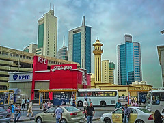 Towers and chicken (Мaistora) Tags: life street city blue red sky people motion color colour detail building cars car yellow mobile architecture modern clouds skyscraper phonecam camphone asian moving gulf traffic cloudy taxi sonyericsson traditional fastfood crowd cellphone mosque busstop arab sandstorm highrise kfc kuwait colourful everyday dust shelter multicultural carpark ethnic beehive contrasts kentuckyfriedchicken topaz expat adjust lowrise taxistand multiethnic denoise topazlabs maistora c905