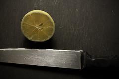 the edge (Prarne) Tags: stilllife kitchen yellow dark handle lemon ominous knife stilleben sharp marks half sliced sour cuttingboard suspense sitron halv kniv