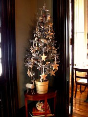 a small silver christmas tree with lots of glass and cream colored ornaments
