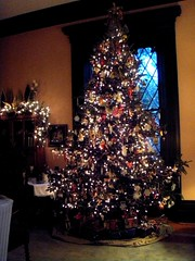 the christmas tree decoratied with many white lights and hundreds of multi colored ornaments