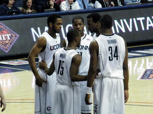 UConn basketball team in a huddle on the court. Photo Credit: Dinur/Flickr