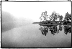 Juuma, Finland - 08/03 (tobydeveson) Tags: bw mist lake reflection nature water fog sunrise 35mm reflections suomi finland island grey landscapes blackwhite skne still grain lakes foggy peaceful naturallight lapland moraines grainy fullframe finn scandinavia uncropped atmospheric kodaktmax400 scania arcticcircle nikomat nikkormat scannedprint rowingboat northerneurope nordiccountries landscapephotography darkroomprint samipeople oulangankansallispuisto scandinavianpeninsula oulankanationalpark juuma treesreflected boatonshore panparks scandinavianmountains suoniemi suomaa worldwidefundfornature kalmarunion skney northernostrobothnia alpinetundraclimate nordiccouncil skainawj scedenig paanajrvinationalpark primefixed24mmlens