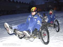 zwei Leute, die im Schnee mit dem Moonbuggy fahren