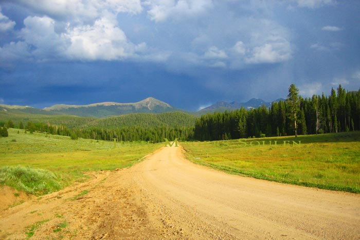 dirt road in Colorado State Forest with stormy sky and mountains