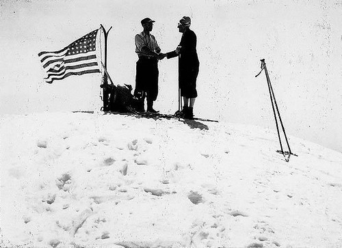 Two skiers atop the summit of Mt. Baker standing next to a U.S. flag