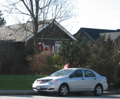 Canadian flags on a house and a car