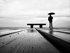 mystic (piriskoskis.) Tags: wood bw man wet rain umbrella bench seaside solitude floor geometry silhouettes bn sp zen lonely maresme loner masnou premia planking zs1 tz6