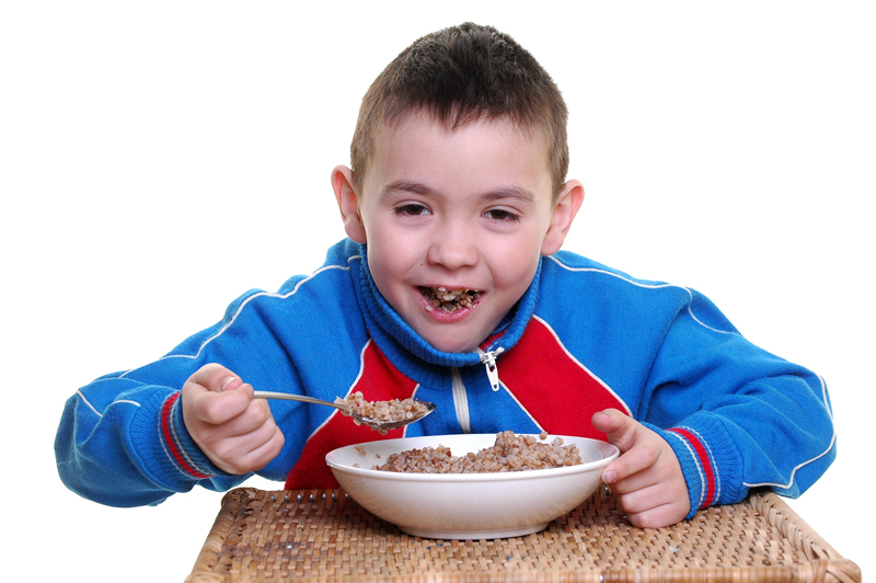 The boy in a sports suit eats a buckwheat cereal