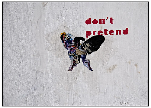 scrapbooked graffiti -- a newspaper butterfly with the words 'don't pretend' up over the right wing