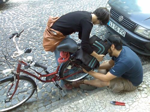 J. a montar uma luz pisca-pisca numa bicicleta de outra participante