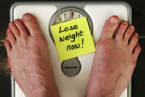 Feet on a body scale with a sticker note saying lose weight now.