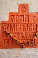 进入城堡,在大门两侧的墙上你会分别看到31个和5个血手印,这是1843年,曼.辛格王公的遗孀们根据传统习俗,陪着丈夫一起火葬自我祭献前留下来的手印,在印度被称为sati。这些血手印是36个女人为夫殉葬前,在手上涂上红色染料然后印上去的。不难想象,这里的每个血手印一定都饱含了太多的无奈、无尽的悲哀、血腥的恐惧和颤抖的绝望。妃子为皇帝殉葬,在历史上并不鲜见,在中国古代大多是赐七尺白绫上吊而亡,或者是活埋致死。但这里的女人更凄惨,这些女人都是在丈夫死后被火化的当天,坐在丈夫的尸体旁被活活烧死的。