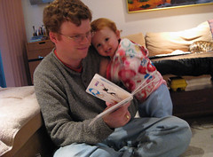Speck's head on Daddy's shoulder, flirting with the camera over top of a book (reading2)