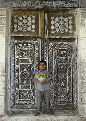 Boy in front of an old door with a bunch of flowers - Ibb - Yemen (Eric Lafforgue) Tags: door boy flower muslim islam arabic yaman kif 0532 jemen arabiafelix  arabieheureuse  arabianpeninsula    imen  jemenas