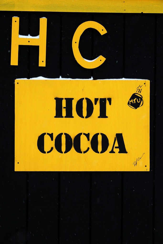 The letters HC and words Hot Cocoa in bright yellow, on a black building