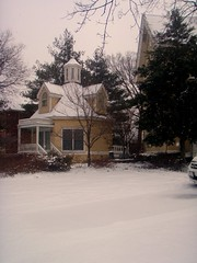 snow on the yard and with the cottage in the background covered in white snow and the green evergreen trees