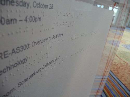 image of a sign at ATIA Chicago, showing the schedule in text and in Braille