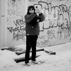 A Kick In The Teeth (Frank Taillandier) Tags: street winter people blackandwhite snow sunglasses mobile graffiti photographer noiretblanc toulouse saintsernin chapka franktaillandier lens:type=35mmf2