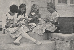 four girls sitting on a step, knitting
