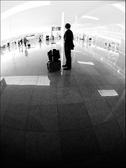 No face for this man. No fate. (Sator Arepo) Tags: leica blackandwhite bw lost airport alone loneliness floor trolley running terminal fisheye explore tiles suitcase frontpage zuiko digilux digilux3 8mmed