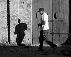 Sempre acompanhado.... (Miriam Cardoso de Souza) Tags: bw textura luz pb porta movimento homem streetshot luzsombra blackwhitephotos neroamet miriamcardosodesouza