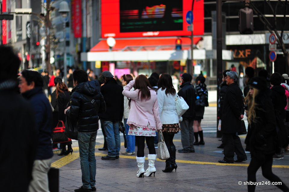 People starting to gather waiting to cross. Shibuya fashion can be bags, clothes or even just face masks.