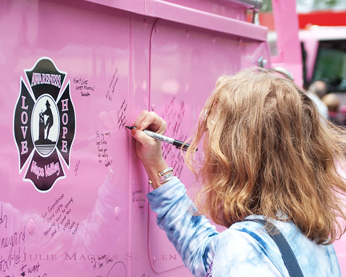 woman signs remembrance on side of pink fire truck