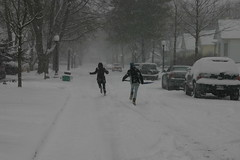 Sarah chasing Rachel with a shovel full of snow