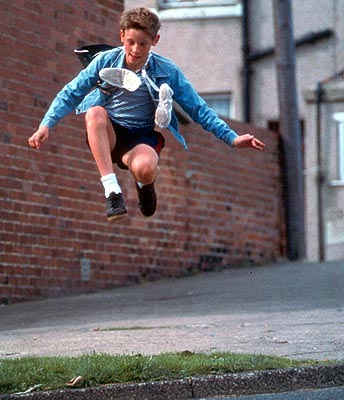 Billy Elliot, a white boy wearing a blue jacket, jumps in the air. Ballet shoes hang around his neck.