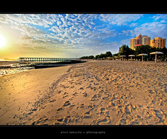 approaching the winter sun [hdr] (alvin lamucho ) Tags: ocean trees winter sea sun building beach clouds umbrella sunrise hotel apartment jetty wide perspective middleeast footprints lowtide kuwait 1022mm hdr fintas egaila rebelt1i alvinlamucho