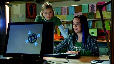 Mac and Veronica are in the computer lab looking at a laptop. Mac, who wears a green shirt with an open blue and green plaid shirt over it and has her hair straight with one blue streak on the left, is sitting in front of the computer and smiling; Veronica, who has short blonde hair in pigtails and is wearing a short-sleeved green t-shirt over a long-sleeved white shirt, is bending down next to her, watching the screen blankly. Several other laptops are visible around them, and a large bulletin board with pastel-papered notices is behind them.