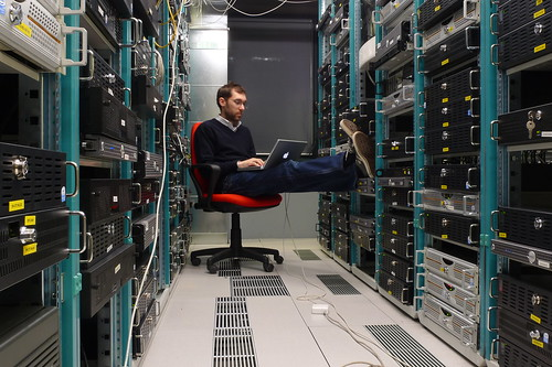 Photograph of a man relaxing in a chair in a datacenter
