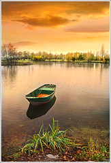 Tranquility (Jean-Michel Priaux) Tags: autumn sunset sky orange sunlight lake france color art nature water grass illustration photoshop automne painting landscape boat fishing pond nikon ship flood dream lac tranquility peinture dreaming bark shore alsace parkway promenade serene bateau paysage seashore tranquilit barque anotherworld tang smallboat mattepainting d90 priaux superaplus aplusphoto digitalflood