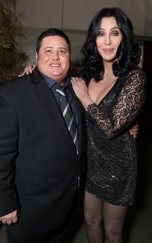 Chaz and his mom, Cher, standing outside of a stone building at nighttime with one arm apiece around the other; Cher has her other arm crossed over her to put her hand on her son's other shoulder. Chaz is wearing a black pinstriped suit over a blue dress shirt and a grey-and-blue tie. Cher, who is half a head taller than him, is wearing a short, sparkly black dress with sleeves made out of black lace and fishnet tights. Both are smiling at the camera. Image via Popsessive.