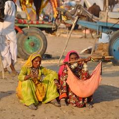 henna appliers (Shreyans Bhansali) Tags: blue portrait woman baby india colorful indian fair camel fabric colourful sack henna pushkar mehndi spitting rajasthan mela rajasthani camelfair pushkarcamelfair2009 appliers