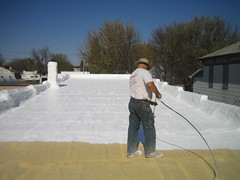 Don Spraying Coating on a Spray Foam Roof
