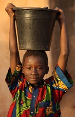 Boy carrying a bucket of water (Raphael Bick) Tags: africa travel burkina fao