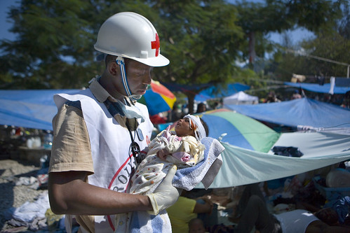 Haitian Red Cross volunteer Jean Zacharie delivers first aid to 1 month old- Deborah Fatima, whose m