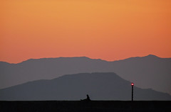(ssj_george) Tags: leica light sunset shadow red sky orange man black mountains nature silhouette wall port landscape island lumix grey harbor alone sitting harbour gray pole panasonic greece single crete layers chania      canea  georgestavrinos fz28 ssjgeorge