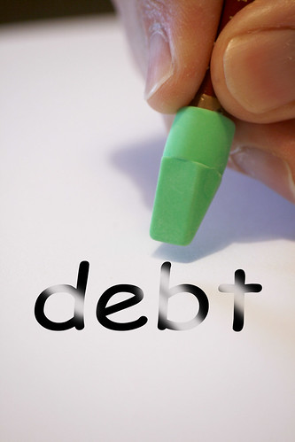 "an eraser being appllied to the word ""debt"" on a piece of paper"