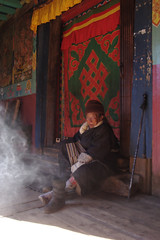Local woman putting on her shoes at Pangboche gompa
