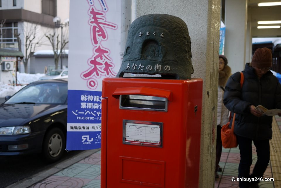 A kamakura decoration on top of the post box outside the station.