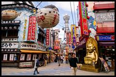 One corner, three Osaka symbols (Eric Flexyourhead) Tags: street city blue red urban signs yellow japan japanese cityscape vibrant vivid kanji  osaka characters colourful kansai clutter  shinsekai billiken tsutenkaku osakatower zd   osakashi naniwaku  zuboraya  1260mm thegodofthingsastheyoughttobe olympuse3