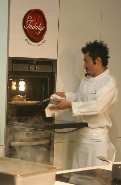 Chef Sho Naganuma removing the roasted baby poussin from the oven