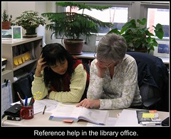 """Librarian working with a student with caption """"Reference help in the library office."""""""