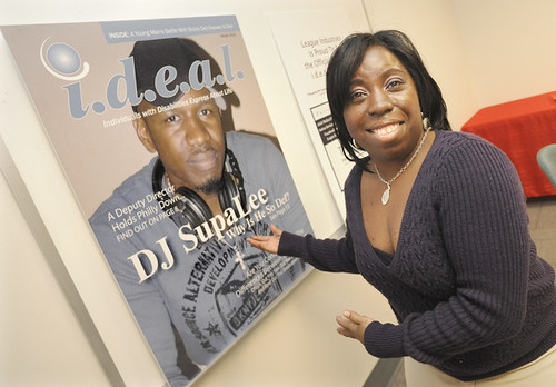 Zarifa Roberson in front of a poster-size front cover of i.d.e.a.l. magazine. DJ SupaLee is on the cover.